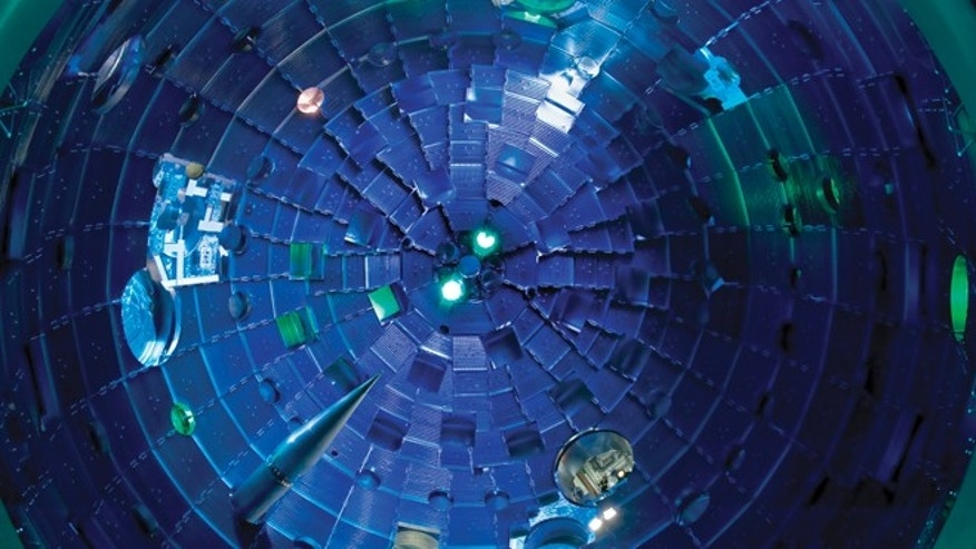 This view from the bottom of the chamber shows the target positioner being inserted. Pulses from NIF's high-powered lasers race toward the Target Bay at the speed of light. They arrive at the center of the target chamber within a few trillionths of a second of each other, aligned to the accuracy of the diameter of a human hair.