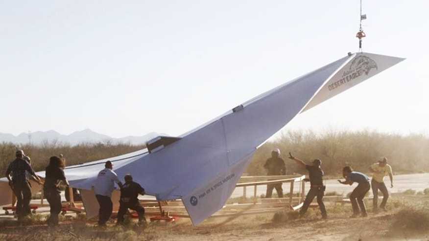 Pima Air & Space Museum launches one of the world's largest paper airplanes across desert near Tucson, Arizona to ignite youth interest in aviation and engineering.