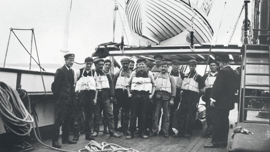 Members of the Titanic crew pose with lifejackets.
