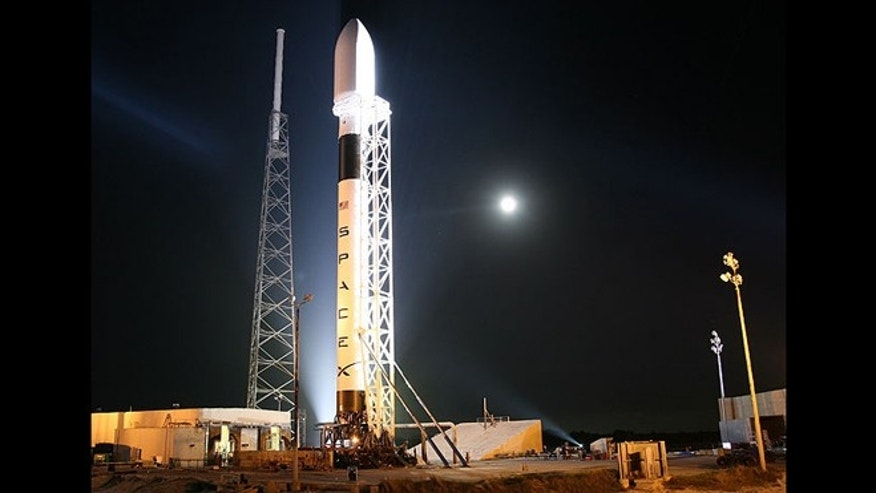 A Falcon 9 rocket from SpaceX sits on a launch pad, awaiting take off.