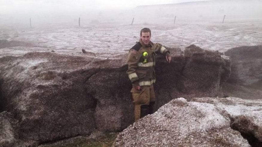 Apr. 11, 2012: A firefighter stands near a shoulder-deep wall of hail, water and ice following storms in northern Potter County, Tex.