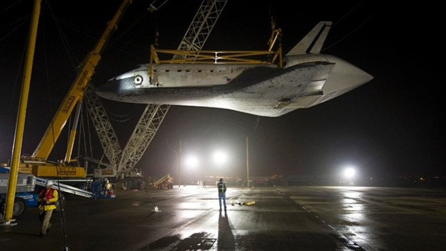 Apr. 19, 2012: The space shuttle Discovery is suspended from a sling held by two cranes after being flown on a the Boeing 747 carrier at Washington Dulles International Airport in Sterling, Va.