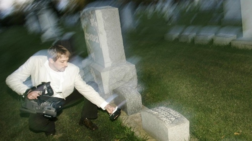 Oct. 31, 2011: Paranormal investigator Noah Voss points a video camera at an electromagnetic frequency device to record any abnormal activity at the Sun Prairie Cemetery in Sun Prairie, Wis.
