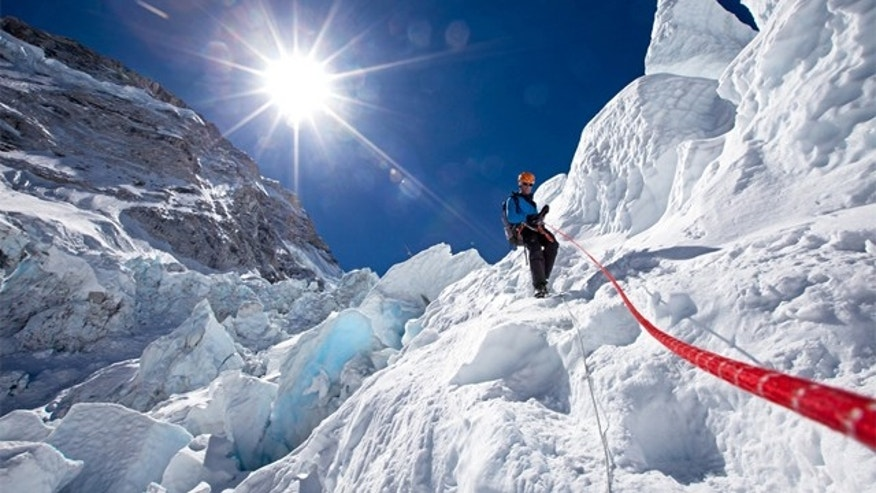 Conrad Anker descending an ice step in the Khumbu Icefall with a fixed rope.