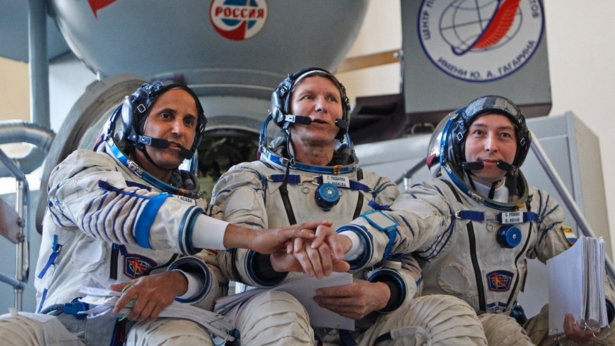 Apr. 24, 2012: Members of the next expedition to the International Space Station, U.S. astronaut Joseph Acaba, left, and Russian cosmonauts Genady Padalka, center, and Sergey Revin, right, shake hands. The three are the next crew scheduled to blast off to the International Space Station from Baikonur cosmodrom on a Russian made Souyz TMA-04M space craft on May 15.