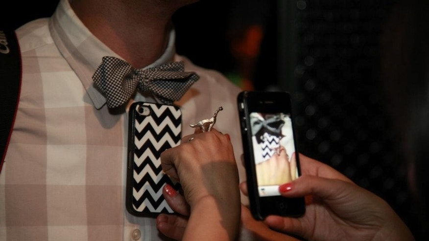 "April 25, 2012: Poshmark ""Posh"" party-goer snapping a picture using their smartphone and listing items for sale via the Poshmark app."