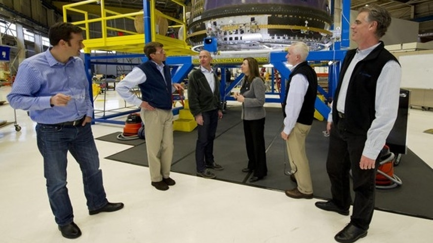 NASA Deputy Administrator Lori Garver, fourth from left, meets Blue Origin founder Jeff Bezos in December 2011, shown next to Blue Origin's crew capsule. Other Blue Origin team members are Bretton Alexander, left; Jeff Ashby, second from left Rob Meyerson, fifth from left, and Robert Millman at the company's headquarters in Kent, Wash.