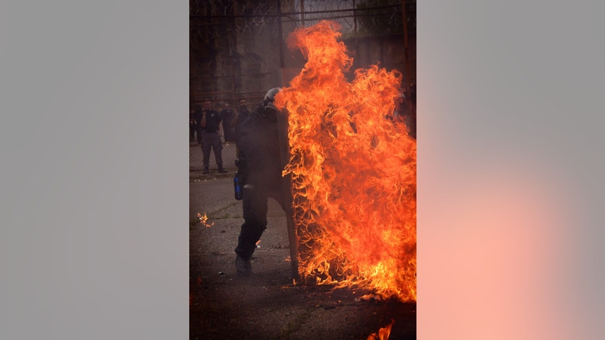 A corrections officer tests fire retardant shields and clothing against a Molotov cocktail during 2011 mock prison riots in West Virginia.