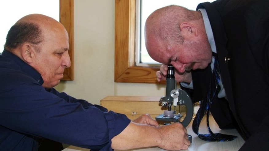 Apr. 23, 2012: Houston-area attorney Joe Gutheinz, right, looks through a microscope at rock particles that Rafael Navarro, left, a former Colombian toy manufacturer, contends are pieces of moon rock in Buffalo, Texas.
