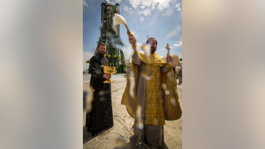 May 14, 2012: An Orthodox Christian priest blesses members of the media shortly after blessing the Soyuz rocket at the Baikonur Cosmodrome Launch pad in Kazakhstan.