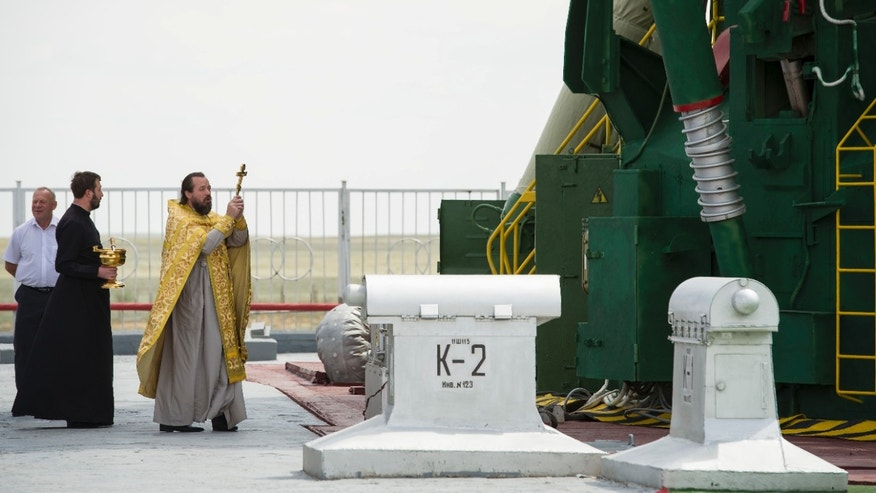 May 14, 2012: An Orthodox Christian priest blesses the Soyuz rocket at the Baikonur Cosmodrome Launch pad in Kazakhstan prior to launch with Expedition 31.