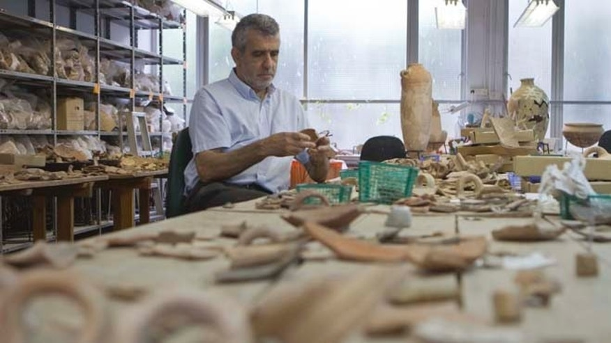 May 23, 2012: Professor Israel Finkelstein sits in his desk at the Tel Aviv University, Israel, where archaeologists have unearthed a stash of rare ancient jewelry near the site of the biblical Armageddon in the north of the country. Finkelstein, who co-directed the dig, said this week that the find offers a rare glimpse into ancient Canaanite high society.