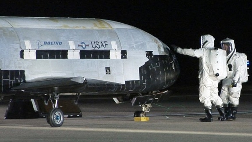 An X-37B robotic space plane sits on the Vandenberg Air Force base runway during post-landing operations on Dec. 3, 2010. Personnel in self-contained protective atmospheric suits conduct initial checks on the robot space vehicle after its landing. This same craft is due to launch again in fall 2012.