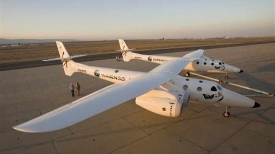 "This July 28, 2008 file photo released by Virgin Galactic shows Sir Richard Branson and designer Burt Rutan walking near the Virgin Mothership WhiteKnightTwo carrier aircraft, or ""Eve,"" in Mojave, Calif. on the eve of its official rollout. The public will get its first in-person glimpse of Virgin Galactic's WhiteKnightTwo carrier aircraft Monday during Experimental Aircraft Association's AirVenture in Oshkosh, Wis."