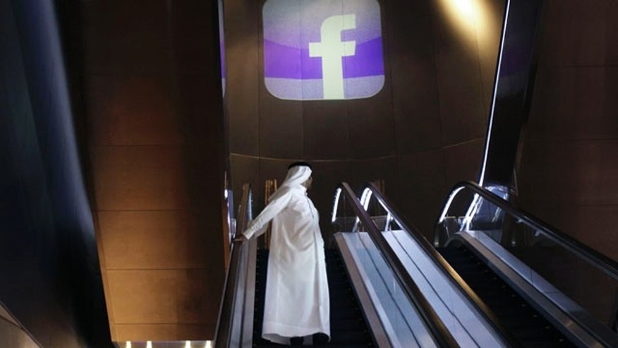An Emirati man stands on an escalator during the Facebook opening of the first Middle East and North Africa office at the Armani hotel in Dubai, United Arab Emirates, Wednesday, May 30, 2012.