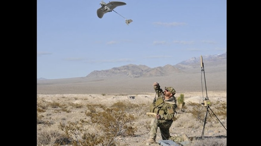 A soldier hald-launches the Wasp AE micro-drone.
