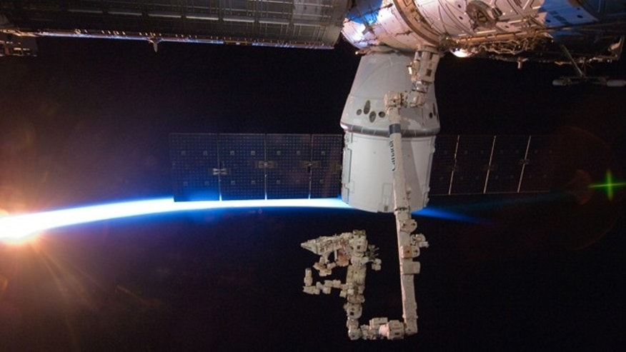 May 27, 2012: With rays of sunshine and the thin blue atmosphere of Earth serving as a backdrop, the SpaceX Dragon commercial cargo craft is berthed to the Earth-facing side of the International Space Station's Harmony node.