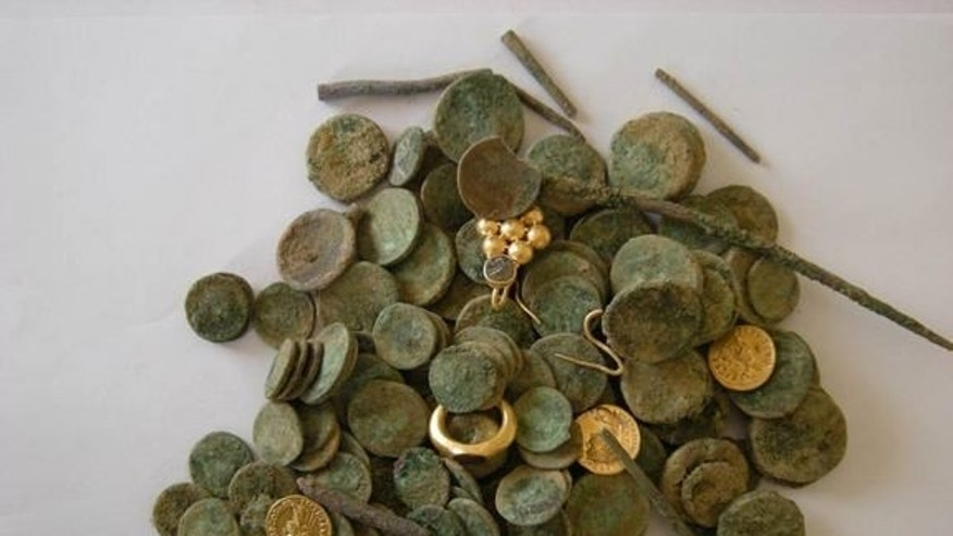 Archaeologists uncovered about 140 gold and silver coins along with gold jewelry in a pit in the courtyard of an exposed building dating to the Roman and Byzantine period.
