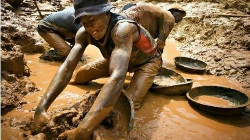 Feb. 23, 2009: A gold miner scoops mud while digging an open pit at the Chudja mine near the village of Kobu in north-eastern Congo.