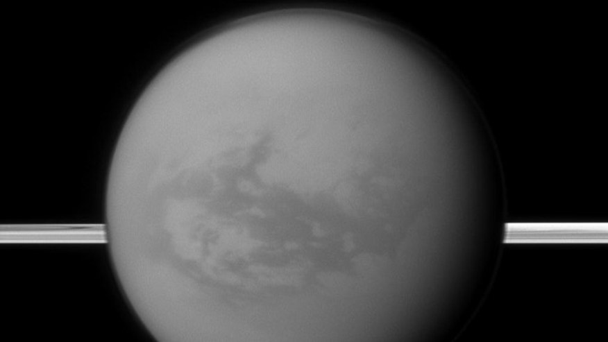 Titan with Saturn's rings in the background. A new study suggests the dark areas near Titan's equator indicate the presence of a hydrocarbon lake and several ponds, a surprise to scientists who thought lakes only existed at the poles.