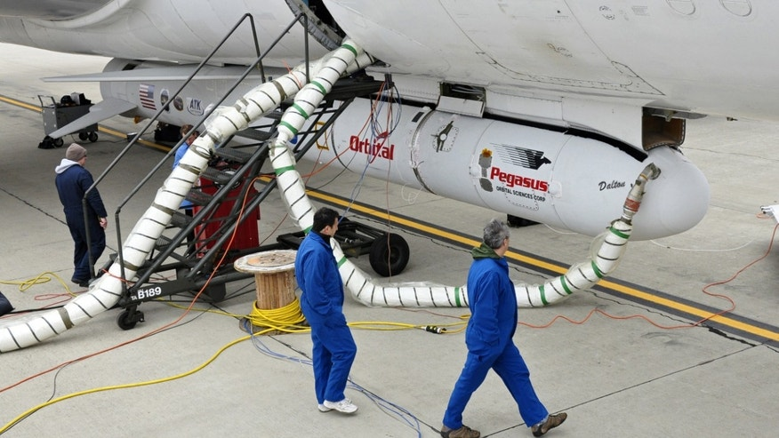 "The Orbital Sciences Corporation Pegasus XL rocket with the NuSTAR spacecraft after attachment to the L-1011 carrier aircraft known as ""Stargazer."""