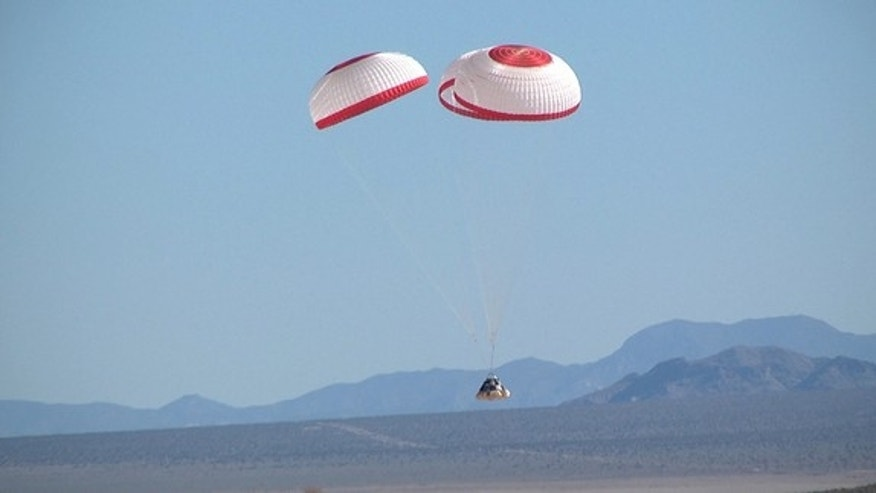 The Boeing CST-100 dangles from a trip of parachutes during a drop test.