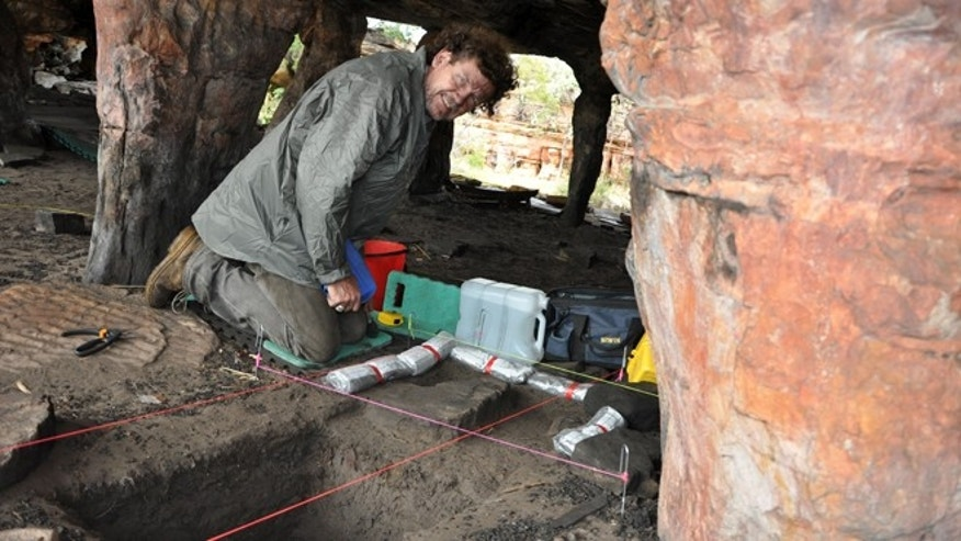 University of Southern Queensland archaeologist Bryce Barker investigates Aboriginal rock art in a cave in the Australian Outback. Prof. Barker said Monday, June 18, 2012, that tests show the Aboriginal rock art in the cave was made 28,000 years ago, making it the oldest in Australia and among the oldest in the world.
