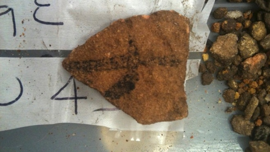 A fragment of Aboriginal rock art on granite found in Australian Outback is seen on a plastic bag.