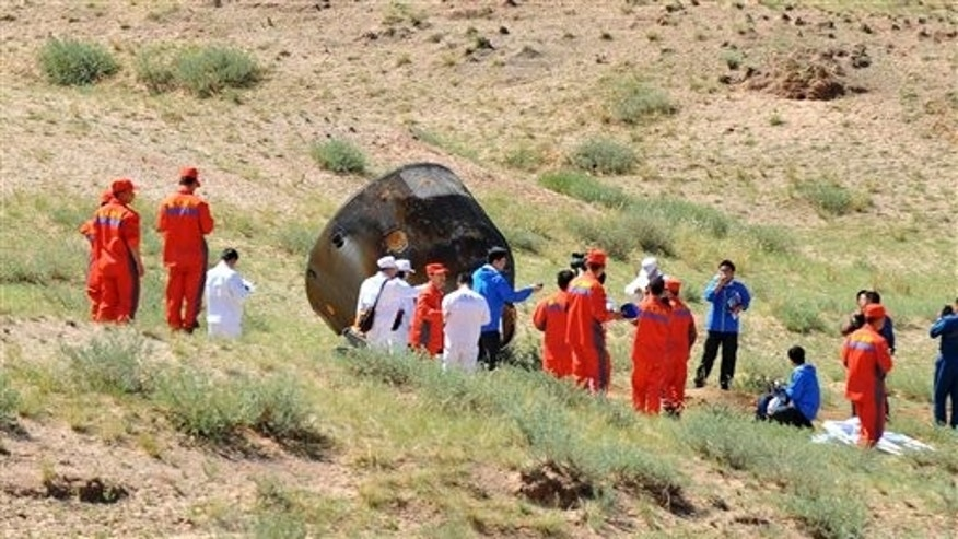 Friday, June 29, 2012: Members of the search team approach the re-entry capsule of China.
