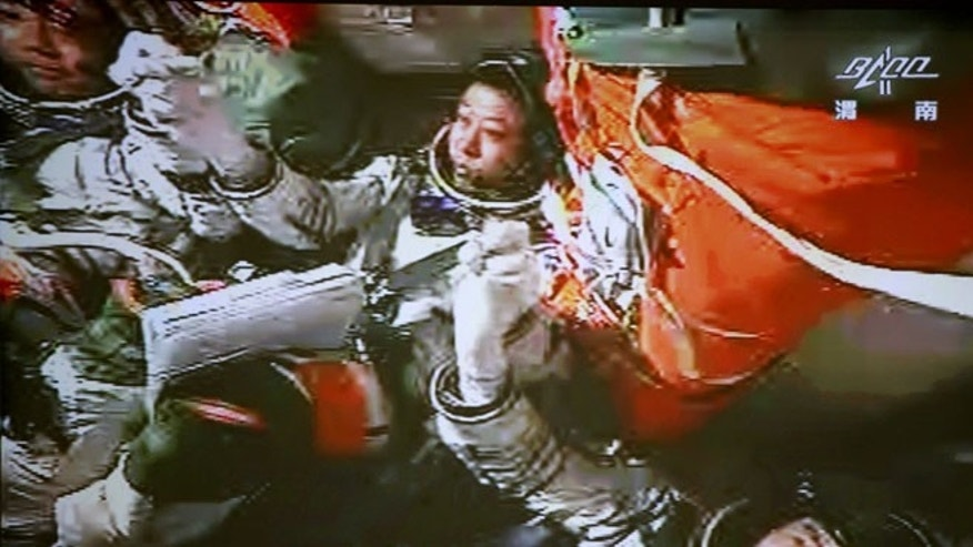 June 24, 2012: In this image made off the monitor screen at the Beijing Aerospace Flight Control Center and released by China's Xinhua News Agency, China's astronauts Jing Haipeng, center, Liu Wang, left, and Liu Yang celebrate inside the Shenzhou-9 manned spacecraft after the success of the manual docking between the spacecraft and Tiangong-1 lab module.