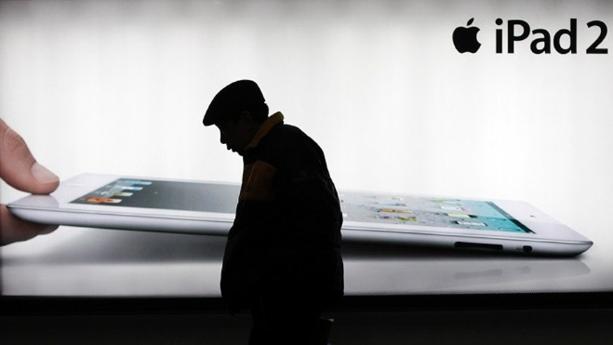 Feb. 28, 2012: FILE - A man walks by an advertisement of Apple's iPad 2 in Shanghai, China.