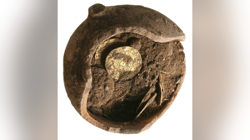 June 25, 2012: Gold coin wink out from beneath the sand of a buried potsherd, uncovered at Apllonia National Park in Israel.