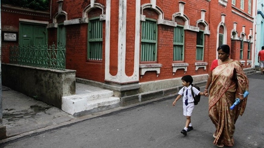 July 10, 2012: A woman and a child walk past the the No. 22, Iswar Mil Lane house where Indian scientist Satyendranath Bose, lived in Kolkata, India. While much of the world was celebrating the international cooperation that led to last week's breakthrough in identifying the existence of the Higgs boson particle, many in India were smarting over what they saw as a slight against one of their greatest scientists.