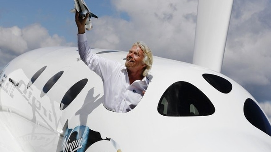 July 11, 2012: Entrepreneur Richard Branson waves a model of the LauncherOne cargo spacecraft from a window of an actual size model of SpaceShipTwo on display, after the LauncherOne announcement and news conference, at the Farnborough Airshow 2012 in southern England.