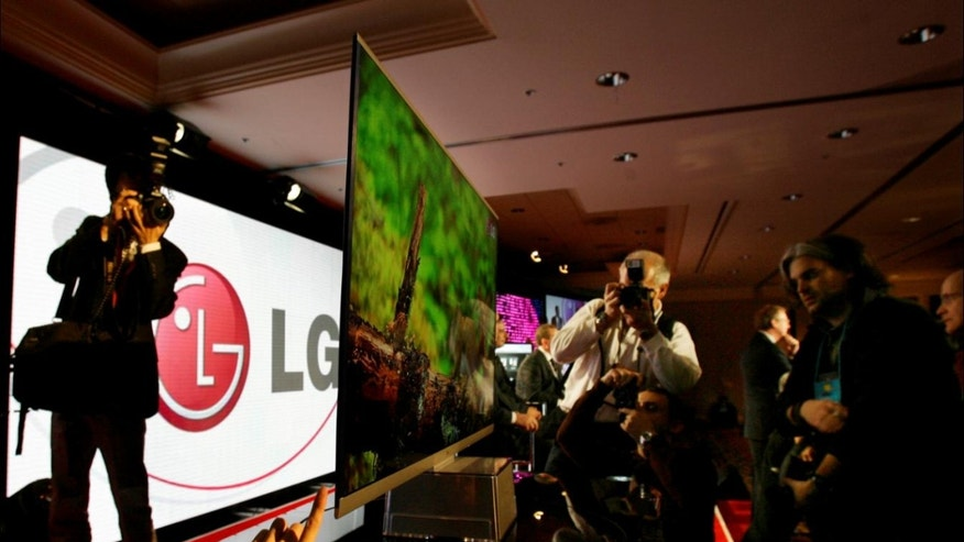 Photographers line up to shoot LG's 6.9 mm screen after it was unveiled during the LG news conference at the International Consumer Electronics Show (CES) in Las Vegas on Wednesday, Jan. 6, 2010.