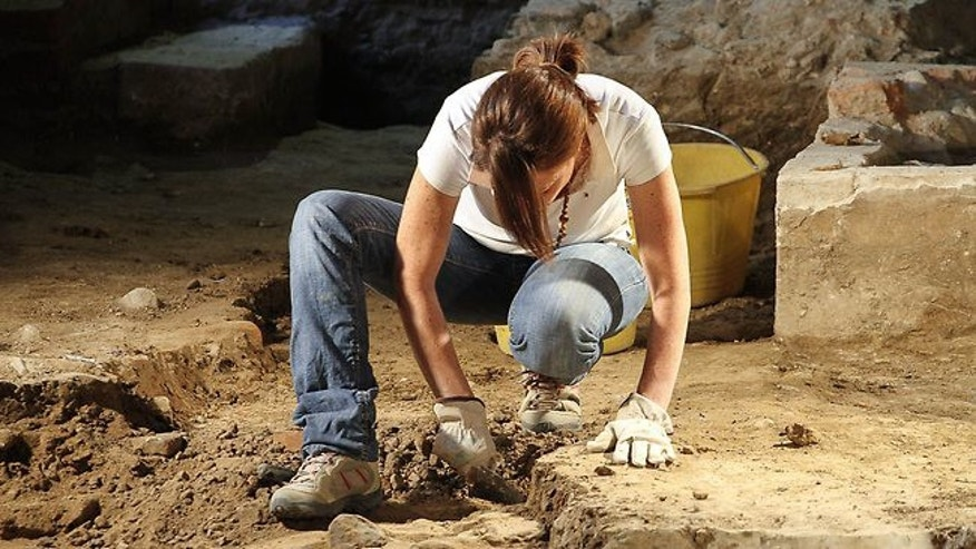 An archaeologist works on the excavation of a grave inside the medieval Convent of Saint Ursula in Florence.