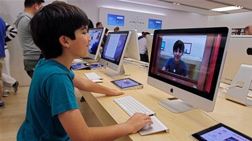 July 19, 2012: In this photo an Apple customer Shayan Hooshmand, 11, uses PhotoBooth on a 21.5-inch iMac at an Apple store in Palo Alto, Calif.