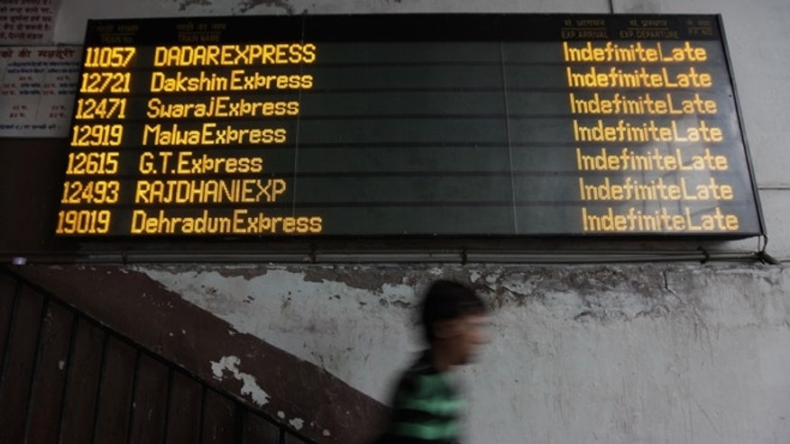 "July 30, 2012: An Indian commuter walks past the status board for trains displaying ""Indefinite Late"" for all the trains following a power outage that struck in the early hours."