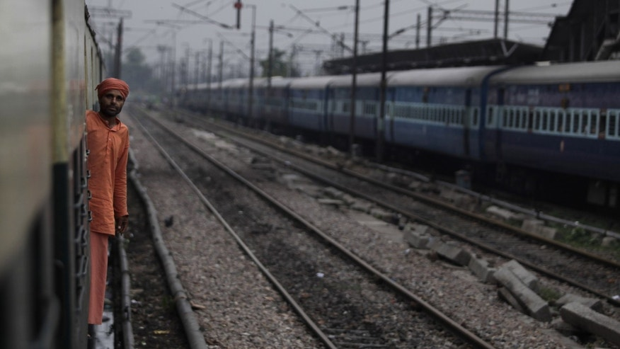 July 30, 2012: An Indian passenger looks out from the compartment of a stationary train following the power outage that struck in the early hours at a train station in New Delhi, India.