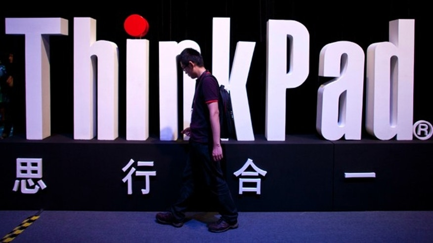 Aug. 6, 2012: A man walks past a ThinkPad logo during a promotional event for the new Thinkpad X1 Carbon laptop in Beijing. The Chinese computer maker says the lighter, quicker ThinkPad was inspired by tablets and smartphones.
