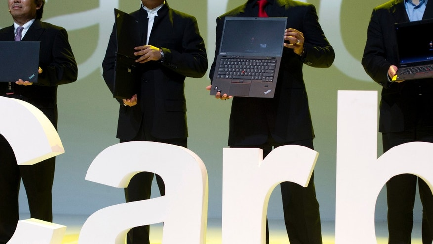 Aug. 6, 2012: Lenovo executives hold the new ThinkPad X1 Carbon laptops in Beijing. The Chinese computer maker unveiled the lighter, quicker ThinkPad notebook computer inspired by the convenience of tablets and smartphones.