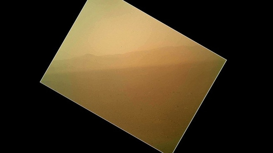 Aug. 7, 2012: The first color view of the north wall and rim of Gale Crater where NASA's rover Curiosity landed Sunday night. The picture was taken by the rover's camera at the end of its stowed robotic arm and appears fuzzy because of dust on the camera's cover.