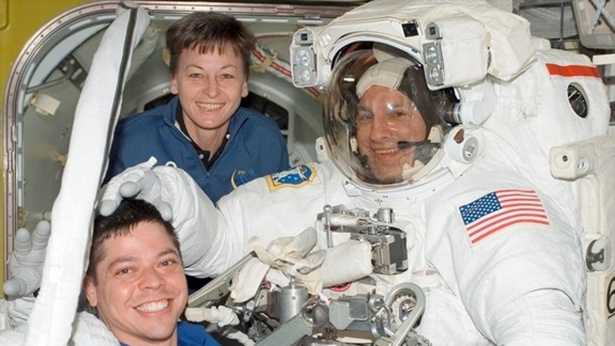 Office, are seen together on board the International Space Station assisting STS-123 mission specialist Rick Linnehan after a spacewalk in March 2008.