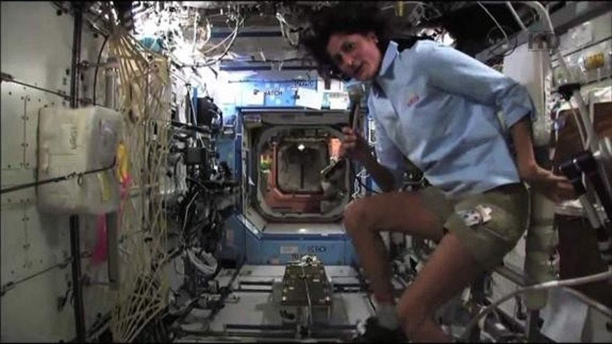 NASA astronaut Sunita Williams demonstrates how to use the International Space Station's exercise bike during an interview with CNN. Williams is training to participate in the Nautica Malibu Triathlon from orbit.