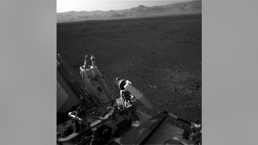 This view shows part of Curiosity rover at bottom with the rim of Gale Crater on Mars in the distance. Image released August 9, 2012.