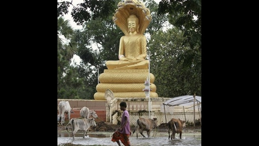 Oct. 13, 2011: A boy walks in flood waters past a Buddha statue in Kampong Thom province.