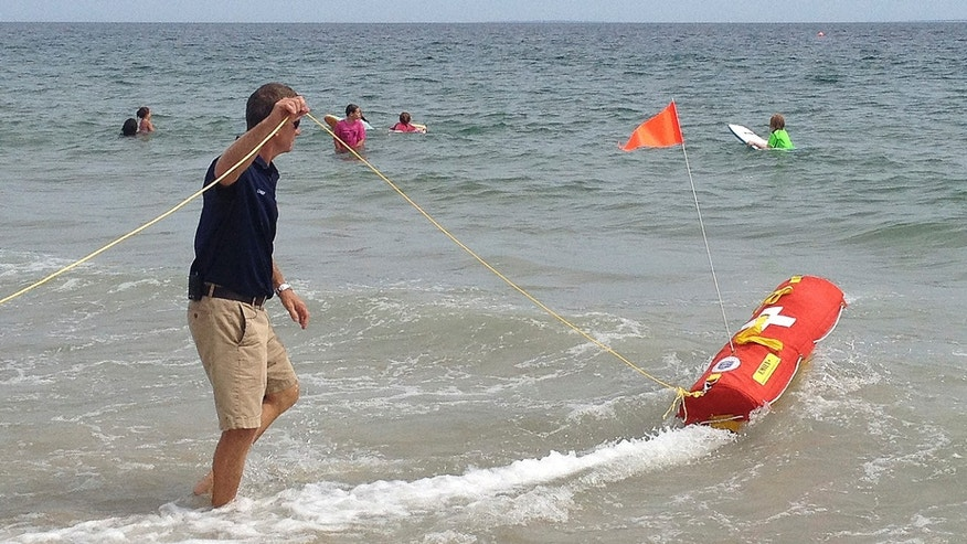 Aug, 8, 2012: Misquamicut, R.I., Fire Chief Louis Misto, left, holds a line attached to the EMILY remote-control lifesaving device as it propels itself in the water and away from the shore at Old Town Beach, in Westerly, R.I.