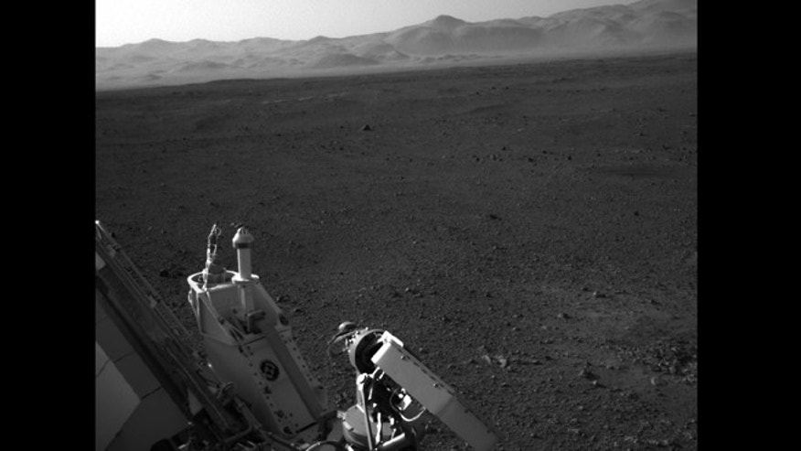 Aug. 7, 2012: NASA's Curiosity rover captures a sliver of itself -- and whole chunk of the Martian landscape, using one of the rover's Navigation cameras looking back over its left shoulder. The rim of Gale Crater is the lighter colored band across the horizon.