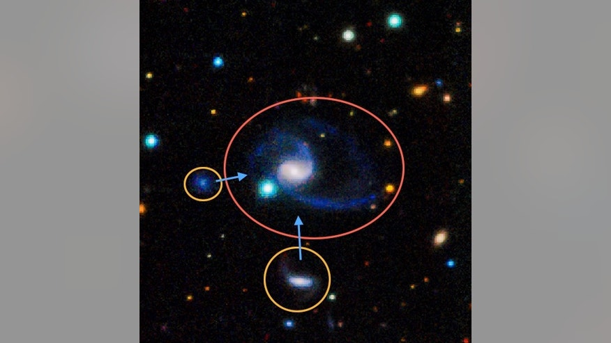 "This image shows one of two ""exact matches"" to the Milky Way galaxy found recently. The larger galaxy, called GAMA202627, clearly has two large companions off to the bottom left. In the image, bluer colors indicate hotter, younger stars, like m"