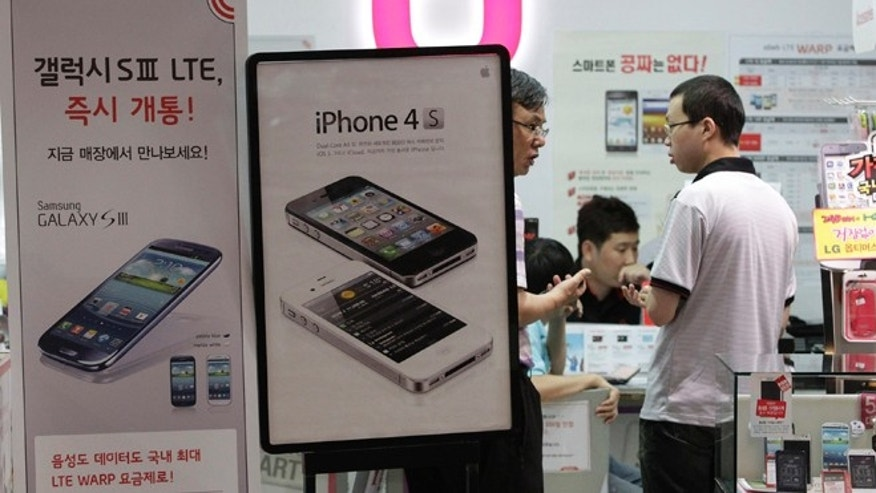 Aug. 24, 2012: Banners advertising Samsung Electronics' Galaxy S III, left, and Apple's iPhone 4S are displayed at a mobile phone shop in Seoul, South Korea. The Seoul Central District Court ruled Friday that technology rivals Apple Inc. and Samsung Electronics Co. both infringed on each other's patents.